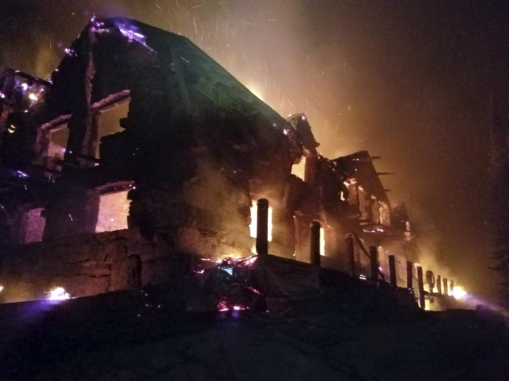 FILE- This Aug. 31, 2017, file image from video provided by the Hutton Incident Team shows the historic main Sperry Chalet building engulfed in flames in Glacier National Park, Mont. Some Montana companies hope to keep the fame of the spruce tree that served as the U.S. Capitol Christmas Tree alive by trucking the tree back home to Montana. Organizers hope it can be used to help rebuild a century-old chalet in Glacier National Park that was destroyed in a wildfire last summer. (Hutton IncidentTeam via AP, File)
