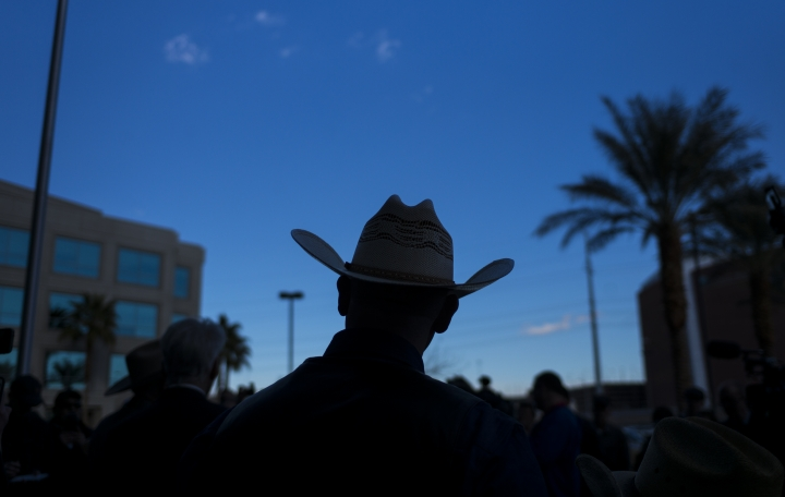 Ryan Bundy, son of rancher Cliven Bundy, listens to his father speak at Metropolitan Police Department headquarters two days after federal charges were dismissed against both of them in Las Vegas on Wednesday, Jan. 10, 2018. Bundy, the Nevada rancher and states' rights figure who was freed after federal charges were dismissed in a 2014 armed standoff with government agents says the county sheriff and the governor are the only authorities he recognizes. (Chase Stevens/Las Vegas Review-Journal via AP)