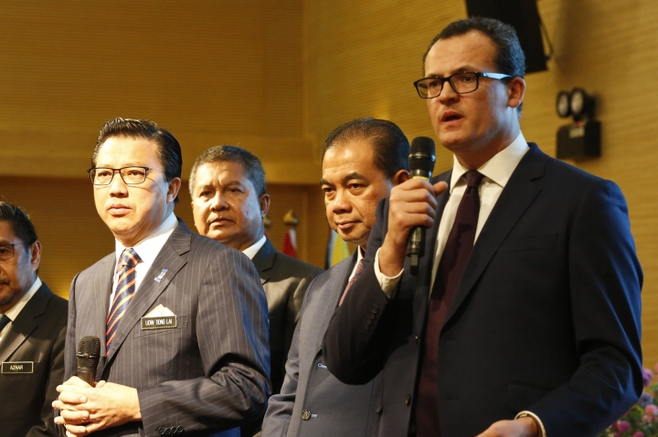 CEO of Ocean Infinity Limited, Oliver Plunkett, right, speaks at a press conference during the MH370 missing plane search operations signing ceremony between the governement of Malaysia and the Ocean Infinity Limited in Putrajaya, Malaysia, Wednesday, Jan. 10, 2018. (AP Photo/Sadiq Asyraf)