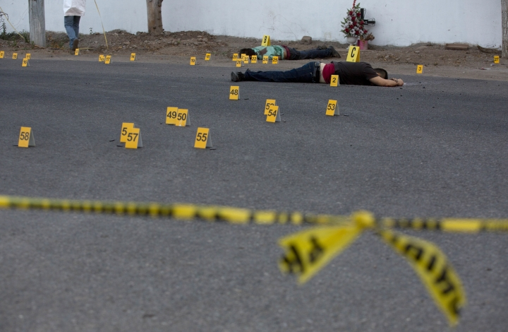 "FILE - In this June 29, 2017 file photo, investigators mark the spot where spent bullet casing fell next several bodies lying on a road in the town of Navolato, Sinaloa state, Mexico. Five states in Mexico have gotten the sternest ""do not travel"" advisories under a revamped U.S. State Department system unveiled Wednesday, Jan. 10 2017. The five include the northern border state of Tamaulipas and the Pacific coast states of Sinaloa, Colima, Michoacan and Guerrero, placing the states on the same level warning level as Somalia, Yemen, Syria or Afghanistan. (AP Photo/Enric Marti, File)"