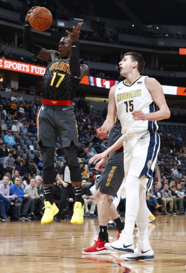 Atlanta Hawks guard Dennis Schroder, left, pulls in a rebound in front of Denver Nuggets center Nikola Jokic, of Serbia, in the first half of an NBA basketball game Wednesday, Jan. 10, 2018 in Denver (AP Photo/David Zalubowski)