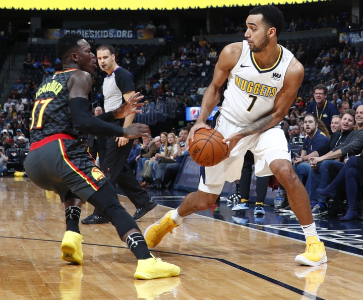 Denver Nuggets forward Trey Lyles, right, looks to pass the ball as Atlanta Hawks guard Dennis Schroder, of Germany, defends in the first half of an NBA basketball game Wednesday, Jan. 10, 2018 in Denver. (AP Photo/David Zalubowski)