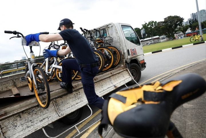 Zhivko Girginov, a Bulgarian living in Singapore, loads up damaged shared bicycles on his lorry to return them to a warehouse after gathering them around his neighbourhood in Singapore, December 29, 2017. REUTERS/Edgar Su