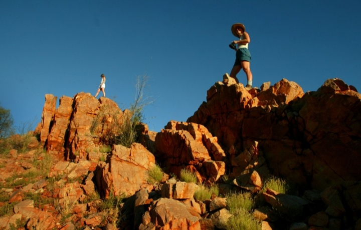 FILE PHOTO: Two tourists watch the setting sun from atop a rocky outcrop in the West MacDonnell Ranges along the Larapinta Trail about 110 kilometres (66 miles) west of the central Australian town of Alice Springs April 18, 2004.   REUTERS/Tim Wimborne/File Photo