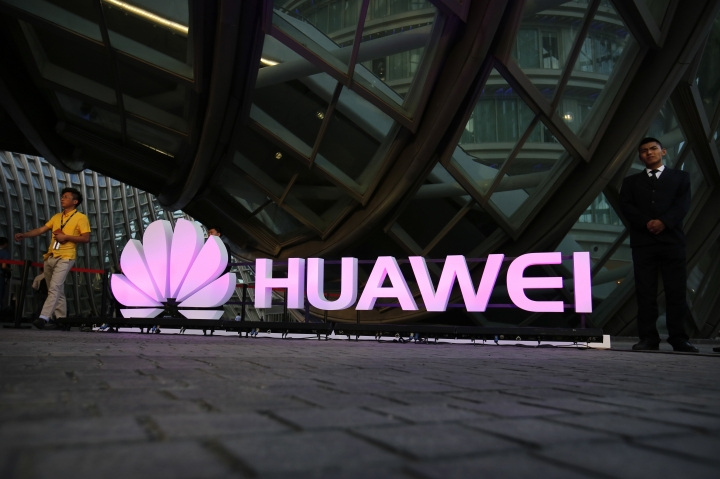 CORRECTS DATE IN THIRD SENTENCE, FILE - In this May 26, 2016 file photo, people walk past an illuminated logo for Huawei at a launch event for the Huawei MateBook in Beijing. A Chinese court notice says homegrown tech giant Huawei has won a patent infringement lawsuit against South Korea smartphone rival Samsung. The notice released Thursday, Jan. 11, 2018 said the court ruled in the Chinese company's favor over two patents involving fourth generation phone technology.(AP Photo/Mark Schiefelbein, File)
