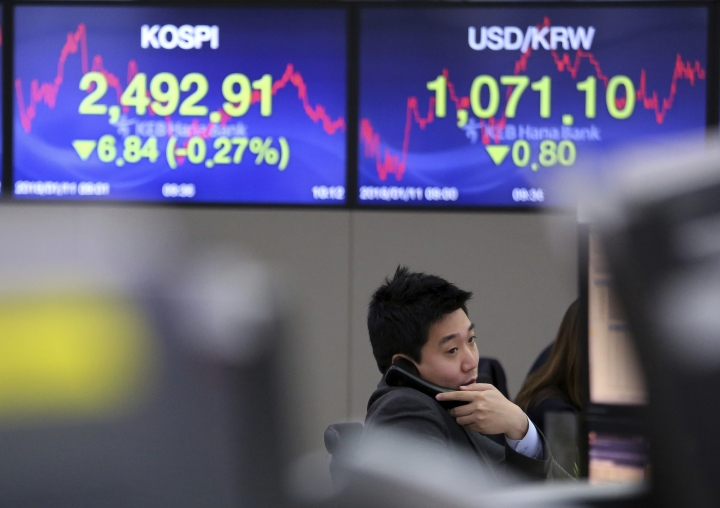 A currency trader talks on the phone at the foreign exchange dealing room of the KEB Hana Bank headquarters in Seoul, South Korea, Thursday, Jan. 11, 2018. Asian stock markets were lower on Thursday after Wall Street posted its first loss this year. Reports that China may slow its purchase of U.S. government bonds weighed on investor sentiment. (AP Photo/Ahn Young-joon)