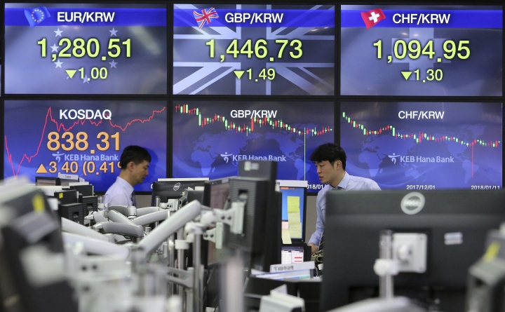 Currency traders work at the foreign exchange dealing room of the KEB Hana Bank headquarters in Seoul, South Korea, Thursday, Jan. 11, 2018. Asian stock markets were lower on Thursday after Wall Street posted its first loss this year. Reports that China may slow its purchase of U.S. government bonds weighed on investor sentiment. (AP Photo/Ahn Young-joon)