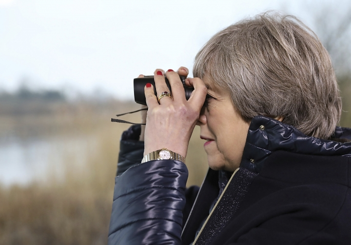Britain's Prime Minister Theresa May looks through binoculars as she watches birds from inside a bird hide with school children at the London Wetland Centre on January 11, 2018 in London, Thursday Jan. 11, 2018. May will launch her 25-year environment plan at the London Wetland Centre on Thursday. (Photo by Dan Kitwood/Getty Images)