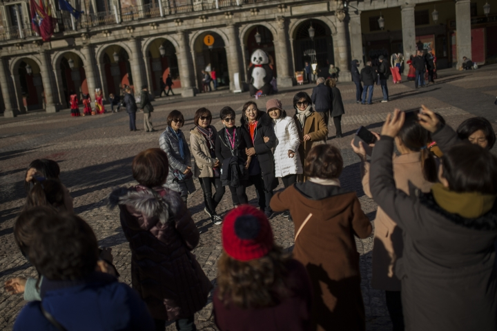 Tourists pose for a photograph at the Mayor square in central Madrid, Thursday, Jan. 11, 2018. Spain says it has broken its record of international visitors for the fifth consecutive year in 2017 with 82 million tourists that chose restive Catalonia as their main Spanish destination. (AP Photo/Francisco Seco)