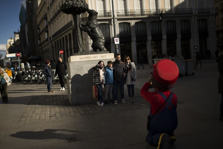 "Tourists pose for a photograph next to the ""Statue of The Bear and The Strawberry Tree"" at Sol square in downtown Madrid, Thursday, Jan. 11, 2018. Spain says it has broken its record of international visitors for the fifth consecutive year in 2017 with 82 million tourists that chose restive Catalonia as their main Spanish destination. (AP Photo/Francisco Seco)"