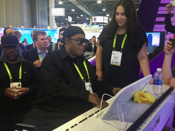 "In this Wednesday, Jan. 10, 2018, photo, musician Stevie Wonder plays a so-called ""smart"" piano, an internet-connected device designed to teach people how to play, while piano teacher Gabie Perry stands next to him at The One Music Group's CES booth in Las Vegas. Wonder spent about 15 minutes playing tunes as a crowd gathered at the booth. Wonder says he likes to visit the conference to see new things and meet people. (AP Photo/Matt O'Brien)"