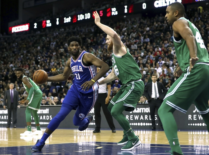 Philadelphia 76ers' Joel Embiid, left, and Boston Celtics' Aron Bynes in action during the NBA London Game 2018 at the O2 Arena in London, Thursday Jan. 11, 2018. (Simon Cooper/PA via AP)