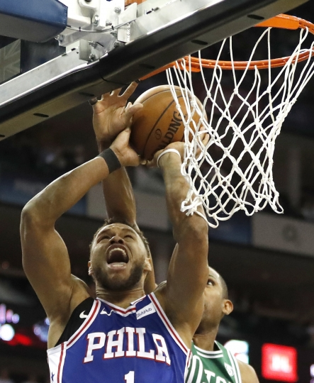 Philadelphia 76ers guard-forward Justin Anderson, left, goes up for a basket during an NBA basketball game between the Boston Celtics and the Philadelphia 76ers at the O2 Arena in London, Thursday, Jan. 11, 2018. (AP Photo/Kirsty Wigglesworth)