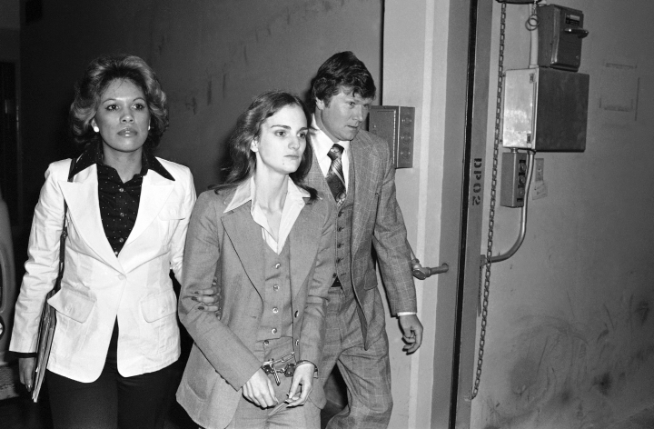 "FILE - In this April 12, 1976 file photo, accompanied by deputy U.S. Marshal John Brophy, Patty Hearst, center, leaves the Federal building in San Francisco, hours after her sentencing on a bank robbery conviction. Twentieth Century Fox Film says on Thursday, Jan. 11, 2018, it is canceling the studio's planned movie based on Jeffrey Toobin's Patricia Hearst book ""American Heiress."" Toobin's non-fiction book chronicled the saga of Hearst's kidnapping by the Symbionese Liberation Army in 1974 and her eventual bank robbery conviction with the radical group. (AP Photo, File)"