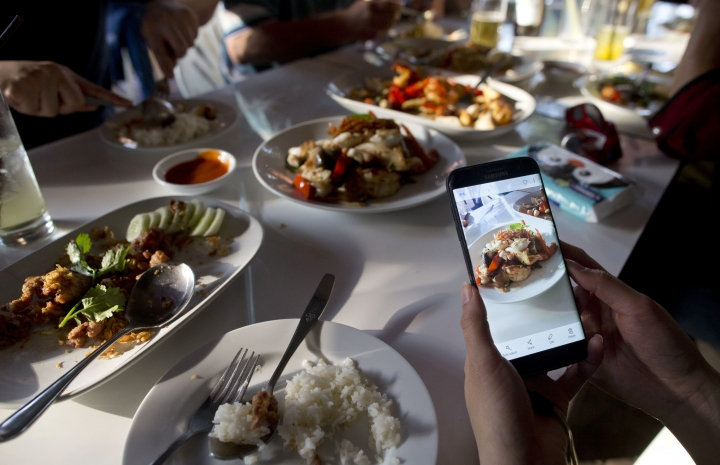 """In this Dec. 20, 2017, photo, a customer takes photos of food cooked by Thai cook Supinya Jansuta, 72, better known as """"Jay Fai,"""" at her eatery in Bangkok, Thailand. After spending more than three decades cooking in an unassuming outdoor kitchen, Jay Fay has been propelled to international culinary stardom by having her restaurant awarded a Michelin star. (AP Photo/Gemunu Amarasinghe)"""