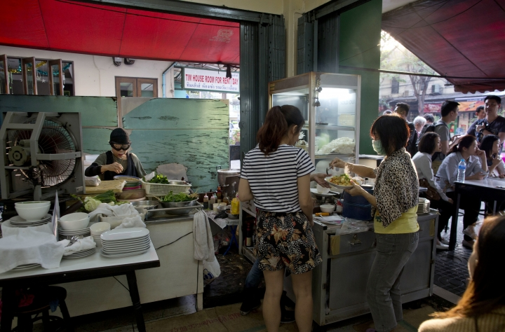 """In this Dec. 20, 2017, photo, Thai cook Supinya Jansuta, left, better known as """"Jay Fai,"""" cooks at her eatery in Bangkok, Thailand. After spending more than three decades cooking in an unassuming outdoor kitchen, Jay Fay has been propelled to international culinary stardom by having her restaurant awarded a Michelin star. (AP Photo/Gemunu Amarasinghe)"""