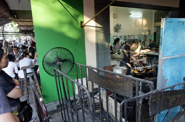 """In this Dec. 20, 2017, photo, customers wait for a table as Thai cook Supinya Jansuta, center, better known as """"Jay Fai,"""" wearing goggles, cooks with two flaming woks at her eatery in Bangkok, Thailand. After spending more than three decades cooking in an unassuming outdoor kitchen, Jay Fay has been propelled to international culinary stardom by having her restaurant awarded a Michelin star. (AP Photo/Gemunu Amarasinghe)"""