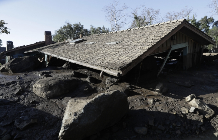 The roof of a structure damaged from storms sits over mud and rocks in Montecito, Calif., Thursday, Jan. 11, 2018. Hundreds of rescue workers slogged through knee-deep ooze and used long poles to probe for bodies Thursday as the search dragged on for victims of the mudslides that slammed this wealthy coastal town. (AP Photo/Marcio Jose Sanchez)