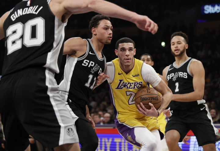Los Angeles Lakers' Lonzo Ball, center right, is defended by San Antonio Spurs' Bryn Forbes during the first half of an NBA basketball game Thursday, Jan. 11, 2018, in Los Angeles. (AP Photo/Jae C. Hong)