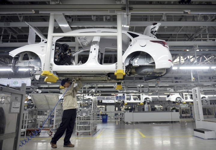 In this Feb. 21, 2017, photo, a staff member works on an assembly line at a Beijing Hyundai Motor auto plant in Cangzhou in northern China's Hebei province. An industry group says China's auto sales shrank in December and ended 2017 up just 1.4 percent over the previous year as the popularity of SUVs helped to offset contraction in demand for sedans. (Chinatopix via AP)