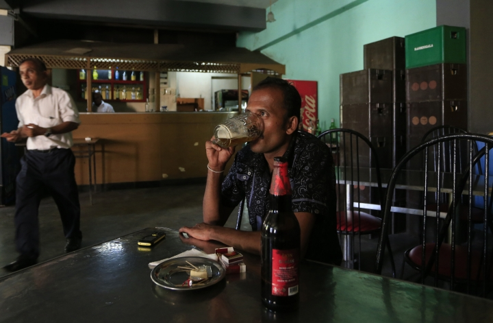 A Sri Lankan man drinks beer at a bar in Colombo, Sri Lanka, Friday, Jan. 12, 2018. Sri Lanka has revoked a 38-year ban on selling alcohol to women and employing them in places where the brews are produced and sold. (AP Photo/Eranga Jayawardena)