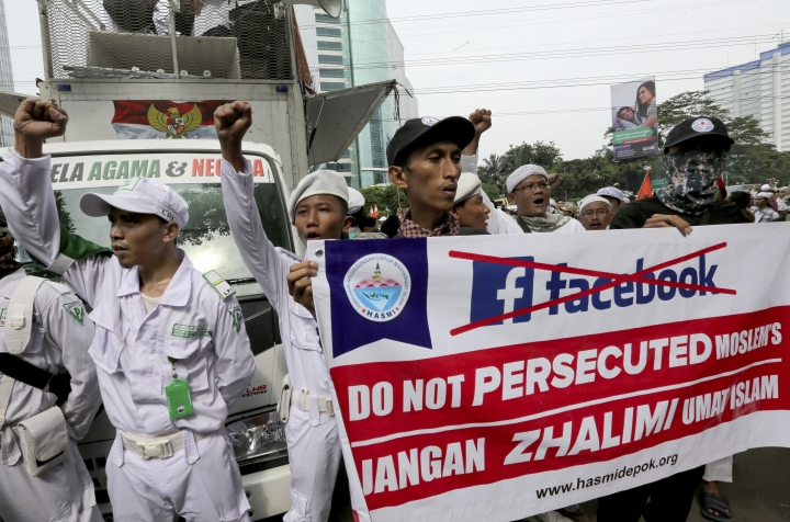 A group of Muslims hold a banner during a rally outside the Facebook office in Jakarta, Indonesia, Friday, Jan. 12, 2018. Muslim hard-liners have staged protest against the social media giant Facebook in Indonesia's capital over its alleged ban on multiple pages and accounts related to their group. (AP Photo/Tatan Syuflana)