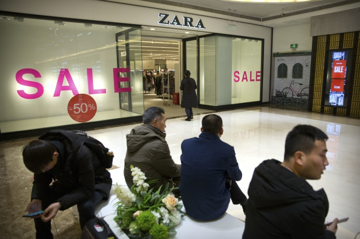 Shoppers look at their smartphones as they sit outside of a Zara store at a shopping mall in Beijing, Friday, Jan. 12, 2018. Chinese regulators have rebuked fashion brand Zara, Delta Air Lines and medical device maker Medtronic for calling Taiwan a country on their websites in a new show of Beijing's intense sensitivity about the self-ruled island. (AP Photo/Mark Schiefelbein)