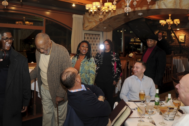 In this Wednesday, Jan. 10, 2018 photo, Bill Cosby passes other diners as he arrives for dinner at an Italian restaurant in Philadelphia. Cosby's new trial on charges he drugged and molested a woman in 2004 was supposed to begin in November, but was delayed until this spring so his new legal team could get up to speed. Jurors deadlocked in June and the judge declared a mistrial. He has said the encounter was consensual. (Tim Gralish/The Philadelphia Inquirer via AP)