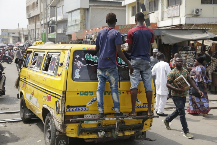 """Two men ride on a back of a commercial bus in Lagos, Nigeria, Friday, Jan. 12, 2018. Africans were shocked on Friday to find President Donald Trump had finally taken an interest in their continent. But it wasn't what people had hoped for. Using vulgar language, Trump on Thursday questioned why the U.S. would accept more immigrants from Haiti and """"shithole countries"""" in Africa rather than places like Norway in rejecting a bipartisan immigration deal. On Friday he denied using that language. (AP Photo/Sunday Alamba)"""