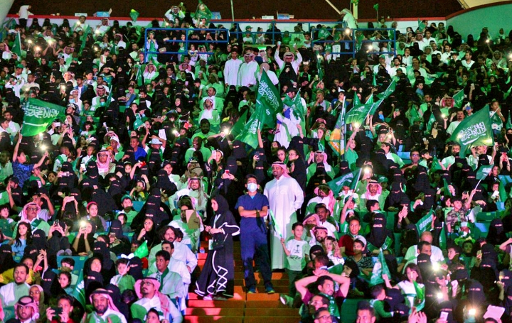 "FILE - In this Sept. 23, 2017 file photo released by Saudi Press Agency, SPA, Saudi men and women attend national day ceremonies at the King Fahd stadium in Riyadh, Saudi Arabia. Saudi women will for the first time be allowed to enter a sports stadium on Friday, Jan. 12, 2018, to watch a soccer match between two local teams — though they will be segregated from the male-only crowd with designated seating in the so-called ""family section."" The move is Saudi Arabia's first social reform planned for this year granting women greater rights. (Saudi Press Agency via AP, File)"