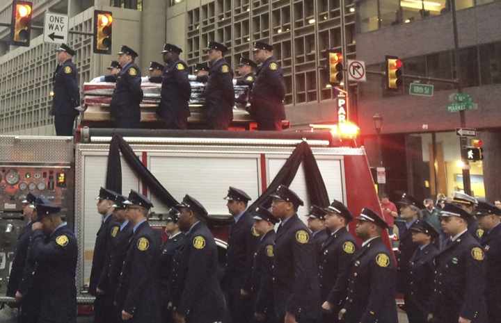 Firefighters line up as the body of Philadelphia firefighter Lt. Matthew LeTourneau is carried on top of a firetruck during a funeral procession on Friday, Jan. 12, 2018 in Philadelphia. Officials say the funeral mass for Lt. Matthew LeTourneau will be held Friday at the Cathedral Basilica of Saints Peter and Paul in Philadelphia. The 11-year veteran was pulled from the home on Saturday by fellow firefighters and taken to a hospital, where he was later pronounced dead. (AP Photo/Kristen DeGroot)