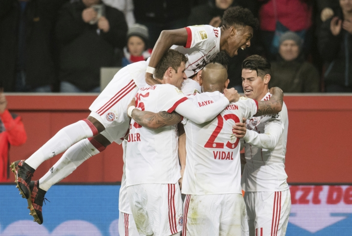 Bayern's David Alaba, top, celebrates the first goal of the game acored by Javi Martinez, obscured, during the German Bundesliga soccer match between Bayer Leverkusen and Bayern Munich in the BayArena in Leverkusen, Germany, Friday Jan. 12, 2018. (Marius Becker/dpa via AP)