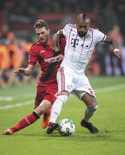 Leverkusen's Lars Bender, left, controls the ball with Bayern's Arturo Vidal, during the German Bundesliga soccer match between Bayer Leverkusen and Bayern Munich in the BayArena in Leverkusen, Germany, Friday Jan. 12, 2018. (Marius Becker/dpa via AP)