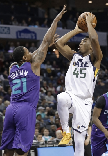 Utah Jazz's Donovan Mitchell (45) shoots over Charlotte Hornets' Treveon Graham (21) during the first half of an NBA basketball game in Charlotte, N.C., Friday, Jan. 12, 2018. (AP Photo/Chuck Burton)