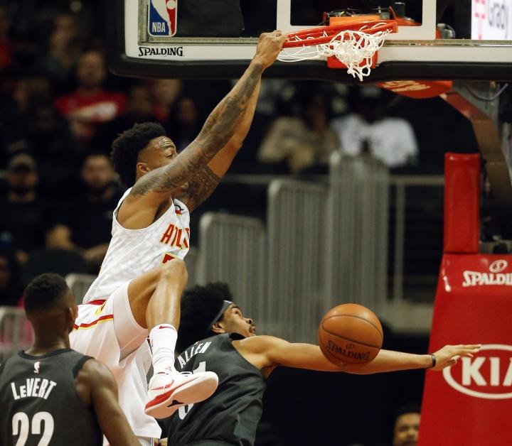 Atlanta Hawks forward John Collins (20) scores as Brooklyn Nets center Jarrett Allen (31) defends in the first half of an NBA basketball game Friday, Jan. 12, 2018, in Atlanta. (AP Photo/John Bazemore)