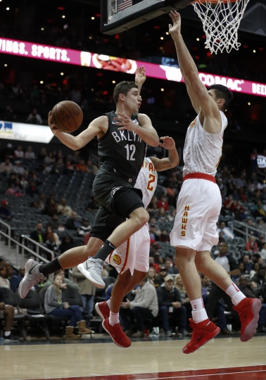 Brooklyn Nets guard Joe Harris (12) passes as Atlanta Hawks' Ersan Ilyasova (7) and Tyler Dorsey (2) defend in the first half of an NBA basketball game Friday, Jan. 12, 2018, in Atlanta. (AP Photo/John Bazemore)