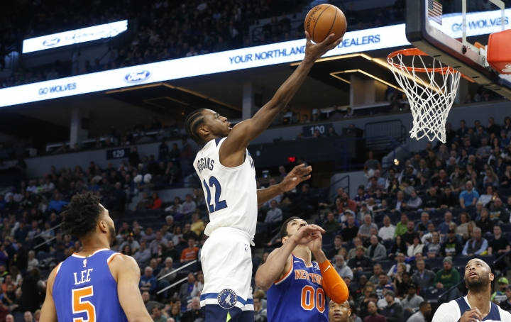 Minnesota Timberwolves' Andrew Wiggins, center, lays up a shot as New York Knicks' Courtney Lee, left, and Enes Kanter, of Turkey, watch in the first half of an NBA basketball game Friday, Jan. 12, 2018, in Minneapolis. (AP Photo/Jim Mone)