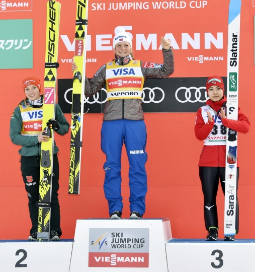Maren Lundby of Norway, center, celebrates her win on the podium, along with second placed Germany's Katharina Althaus and third placed Japan's Sara Takanashi, during a World Cup ski jumping event in Sapporo, northern Japan, Saturday, Jan. 13, 2018. (Nobuki Ito/Kyodo News via AP)