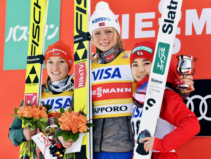 Maren Lundby of Norway, center, celebrates her win on the podium, along with second placed Germany's Katharina Althaus, left, and third placed Japan's Sara Takanashi, right, during a World Cup ski jumping event in Sapporo, northern Japan, Saturday, Jan. 13, 2018. (Nobuki Ito/Kyodo News via AP)