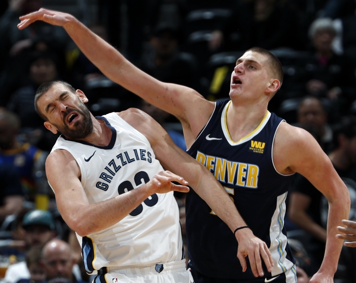 Memphis Grizzlies center Marc Gasol, left, of Spain, reacts after he was hit on the head while fighting for a rebound with Denver Nuggets center Nikola Jokic, of Serbia, in the first half of an NBA basketball game Friday, Jan. 12, 2018, in Denver. (AP Photo/David Zalubowski)