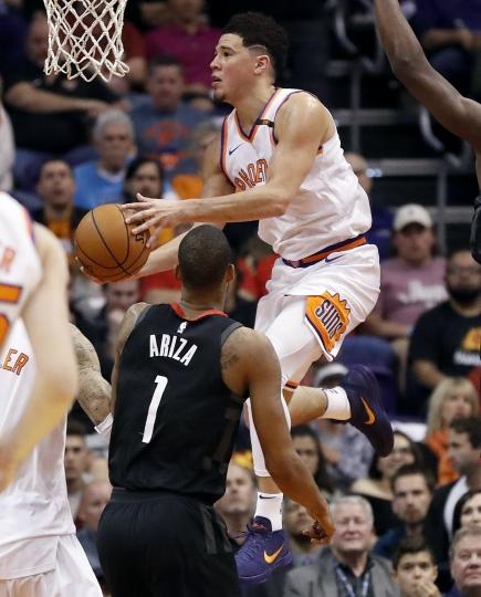 Phoenix Suns guard Devin Booker drives over Houston Rockets forward Trevor Ariza (1) during the first half of an NBA basketball game, Friday, Jan. 12, 2018, in Phoenix. (AP Photo/Matt York)