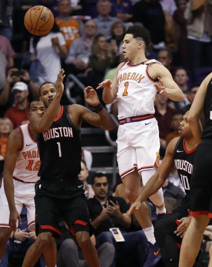 Phoenix Suns guard Devin Booker passes the ball past Houston Rockets forward Trevor Ariza,front left, during the first half of an NBA basketball game Friday, Jan. 12, 2018, in Phoenix. (AP Photo/Matt York)
