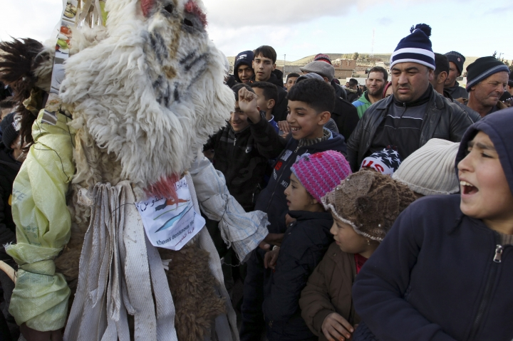 Performers dressed in animal-hide costumes greet children as part of the Ayred festival in the village of Beni Snous, south of Tlemcen, Algeria, Thursday, Dec.11, 2018. The three-day annual festival highlights agricultural traditions of the Amazigh, or Berbers, and celebrates the victory of a Berber king in 950 BC over armies of the Egyptian pharaoh seeking to colonize the region. (AP Photo/Anis Belghoul)