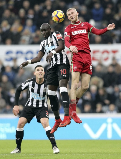 Newcastle United's Mohamed Diame, center, and Swansea City's Oliver McBurnie battle for a header during the English Premier League soccer match against Swansea City at St James' Park, Newcastle, England, Saturday Jan. 13, 2018. (Owen Humphreys/PA via AP)