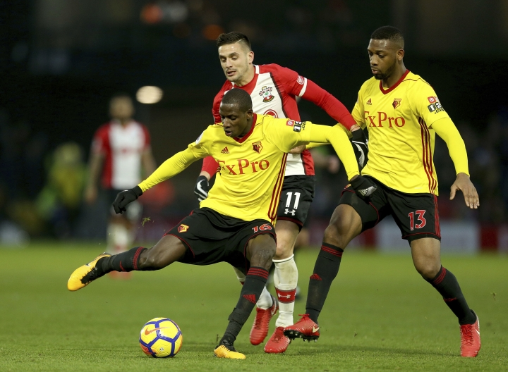 Watford's Abdoulaye Doucoure, left, and Southampton's Dusan Tadic, center, battle for the ball during the English Premier League soccer match at Vicarage Road, Watford, England, Saturday Jan. 13, 2018. (Steven Paston/PA via AP)