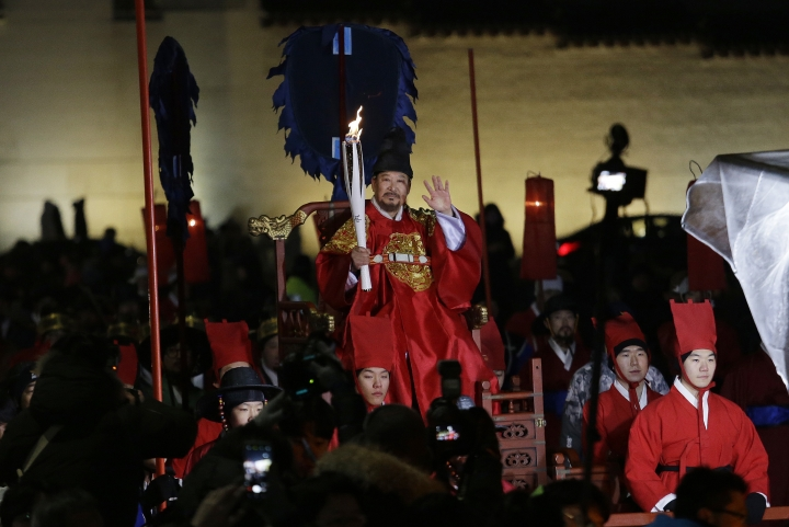 A torch bearer wearing traditional Korean king costume carries the torch during the Olympic Torch Relay in Seoul, South Korea, Saturday, Jan. 13, 2018. South Korea said Saturday that North Korea proposed that their talks next week address a North Korean art troupe's visit to the Pyeongchang Winter Olympics in the South, rather than the participation of the nation's athletes. (AP Photo/Ahn Young-joon)