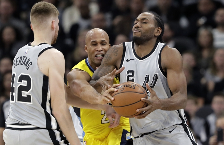 San Antonio Spurs forward Kawhi Leonard (2) is pressured by Denver Nuggets forward Richard Jefferson, center, during the first half of an NBA basketball game Saturday, Jan. 13, 2018, in San Antonio. (AP Photo/Eric Gay)