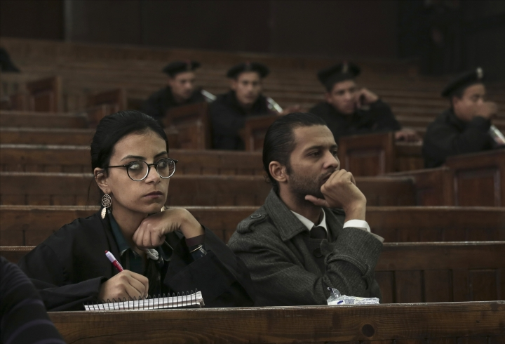 FILE - In this Dec. 4, 2014 file photo, Mahienour el-Masry, left, a prominent activist and rights lawyer, takes notes during a trial of activists, in Cairo, Egypt. In a verdict issued late Saturday, Jan. 13, 2018, an appeals court in Alexandria, Egypt acquitted el-Masry of charges of taking part in an illegal demonstration. El-Masry was convicted and sentenced to two years in prison last month over participating in a protest against the government's transfer of two strategic Red Sea islands to Saudi Arabia. (AP Photo/Nariman El-Mofty, File)