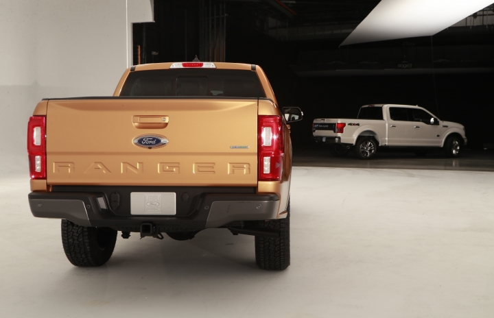 This Jan. 5, 2018, photo shows the 2019 Ford Ranger, foreground, and the F-150 in a studio in Warren, Mich. Ford is unveiling the North American version of the Ranger on Sunday, Jan. 14, ahead of the Detroit auto show. It goes on sale next spring, eight years after Ford pulled it off the market in the U.S. and Canada. (AP Photo/Carlos Osorio)