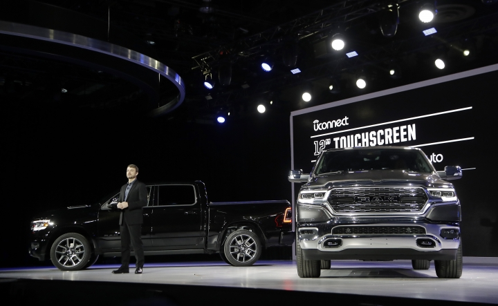 Mike Manley, head of Ram, stands next to a pair of 2019 Ram 1500 pickups during the North American International Auto Show, Monday, Jan. 15, 2018, in Detroit. (AP Photo/Carlos Osorio)